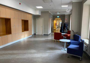 En tom korridor i skolan med stolar och några bord